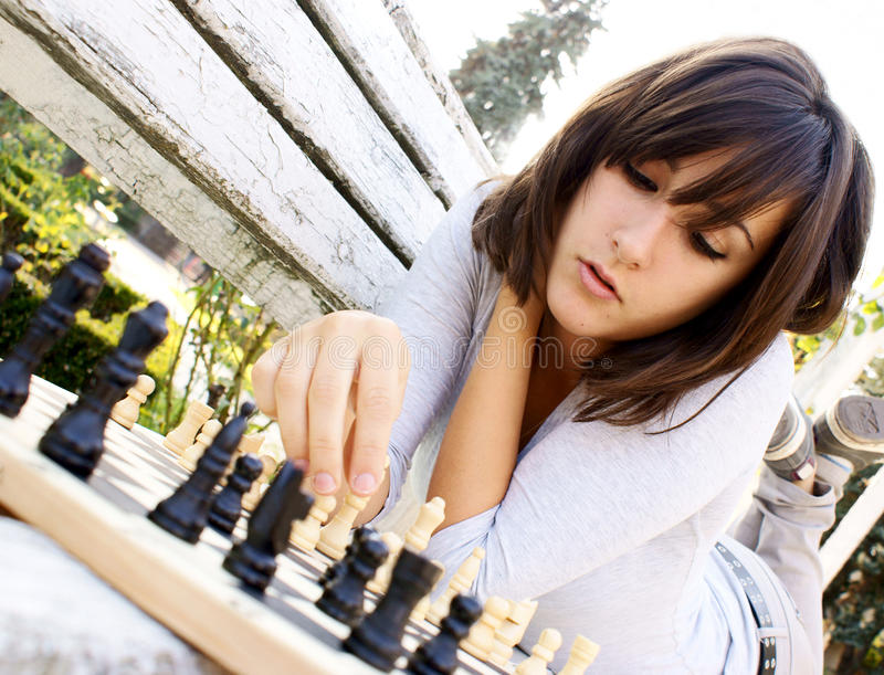 Young beautiful woman playing chess stock images