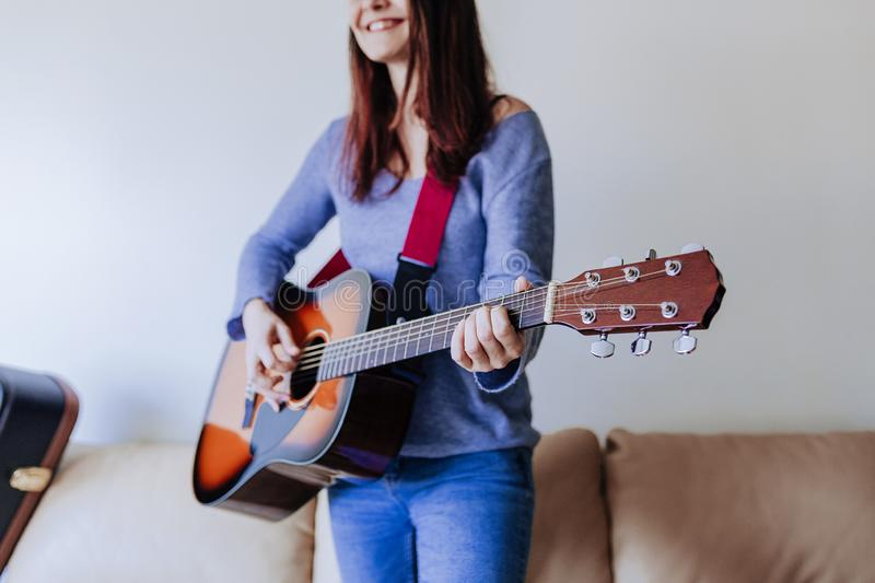 Young beautiful woman playing guitar standing on the sofa. Music concept. Portrait drive home inspiration bedroom band electric rock expression female freedom royalty free stock photography
