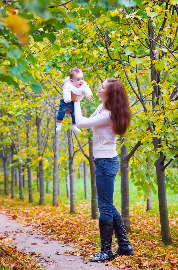 Young beautiful woman playing with her baby in a park royalty free stock photo