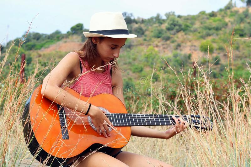 Young and Beautiful Woman playing spanish guitar outdoors in the forest royalty free stock image