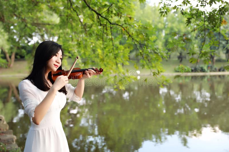 Young woman playing violin ,Silhouette of teenage violin player over sunset on river,lake stock images