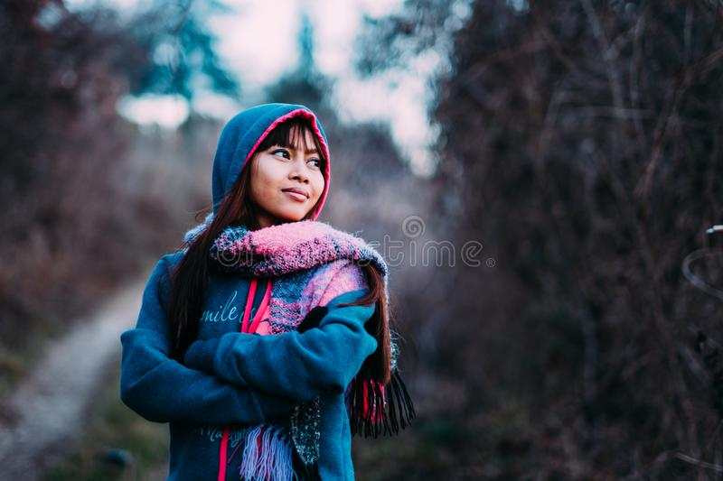 Young beautiful woman portrait in cold weather wearing sweater and colorful scarf during afternoon outside.  stock images