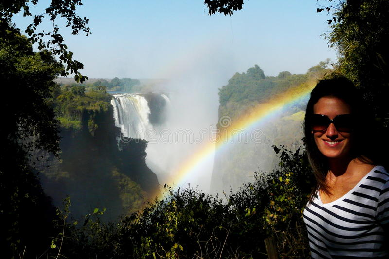 Young beautiful woman portrait with Victoria Falls on background, Zimbabwe's border line with Zambia, Africa.  stock photography