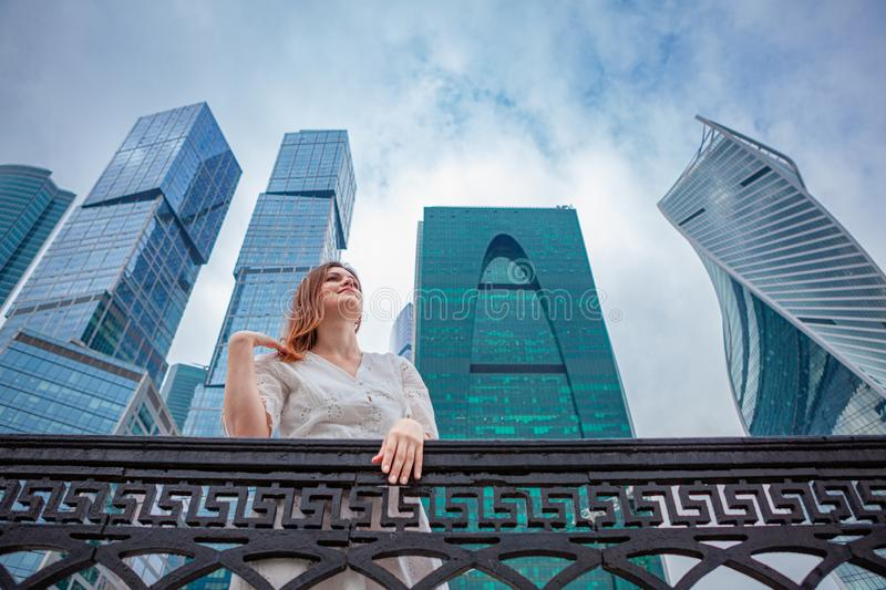 Young woman posing on skyscrapers background. Young beautiful woman posing on Moscow`s skyscrapers background stock image