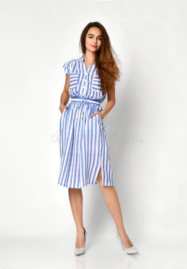 Young beautiful woman posing in new blue stripes casual summer dress on grey royalty free stock photo
