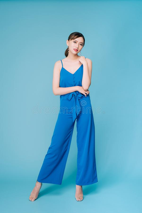 Young beautiful woman posing in new casual blue fashion costume dress with pants full body on blue background.  stock photography