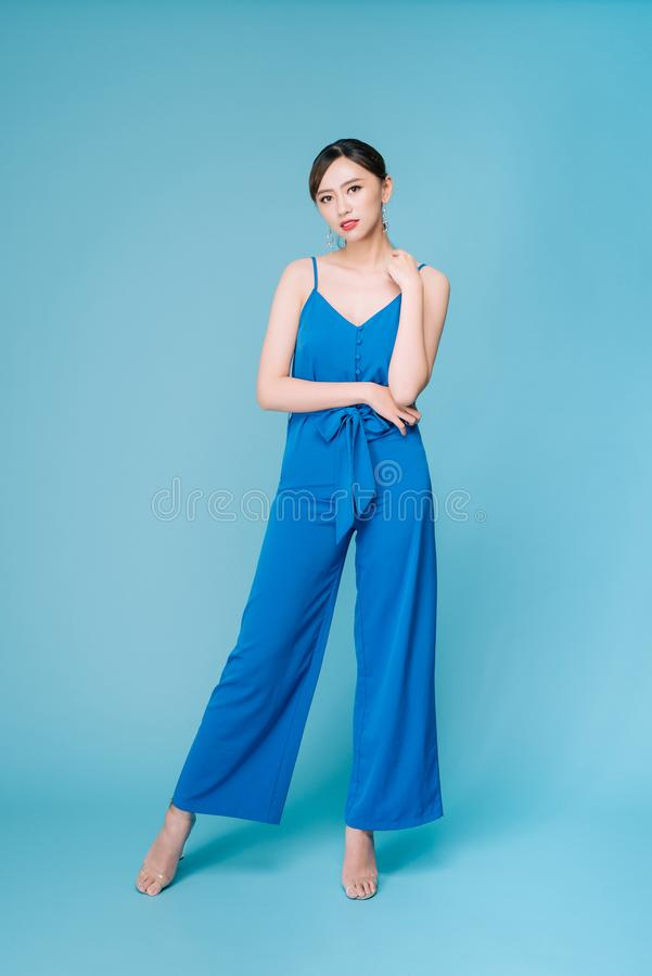 Young beautiful woman posing in new casual blue fashion costume dress with pants full body on blue background royalty free stock photography