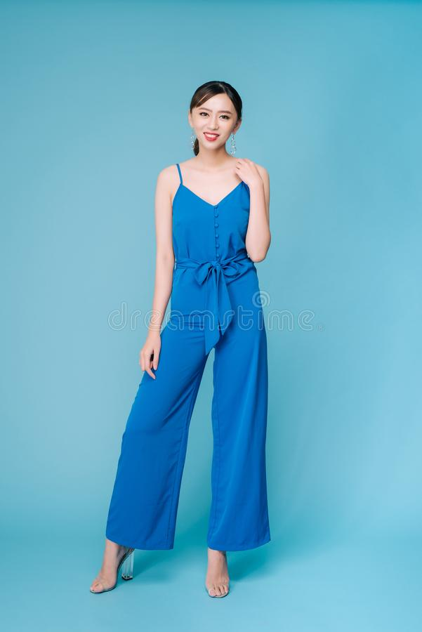 Young beautiful woman posing in new casual blue fashion costume dress with pants full body on blue background.  stock photo