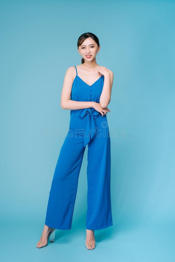 Young beautiful woman posing in new casual blue fashion costume dress with pants full body on blue background.  royalty free stock photography