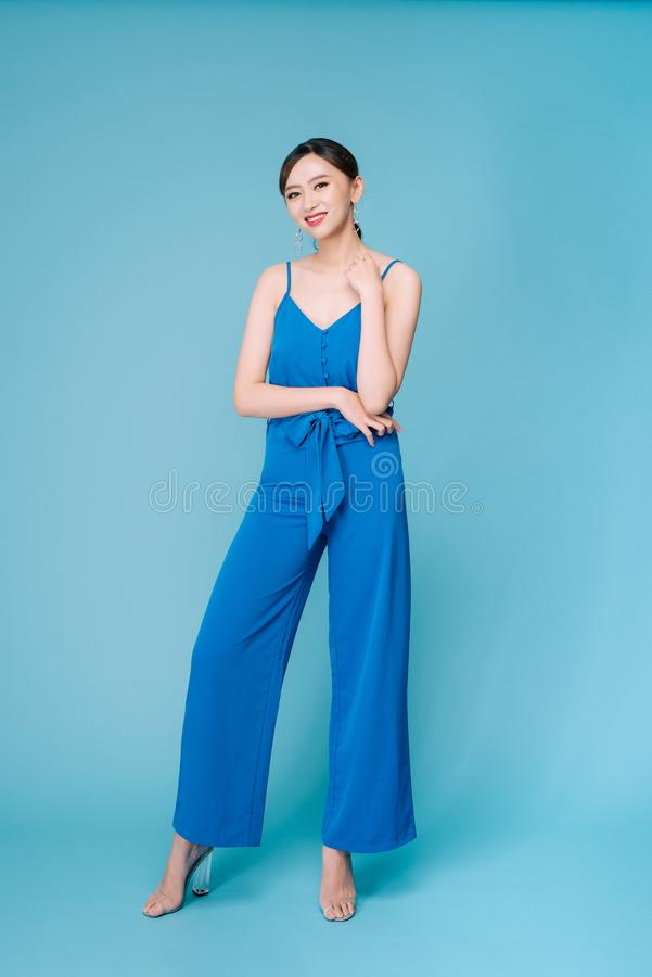 Young beautiful woman posing in new casual blue fashion costume dress with pants full body on blue background.  stock image