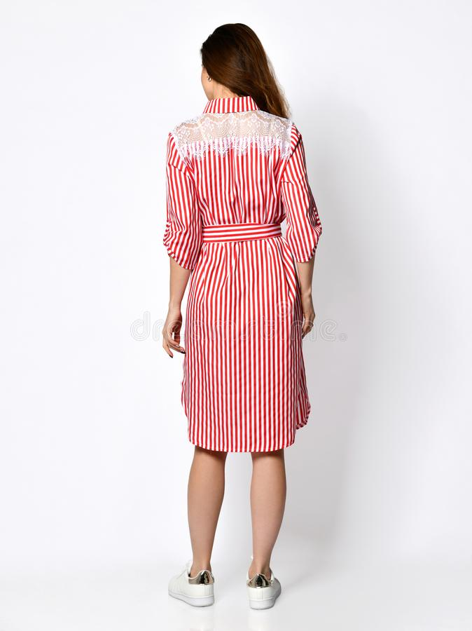 Young beautiful woman posing in new casual light pink red stripes dress back side rear view royalty free stock photos