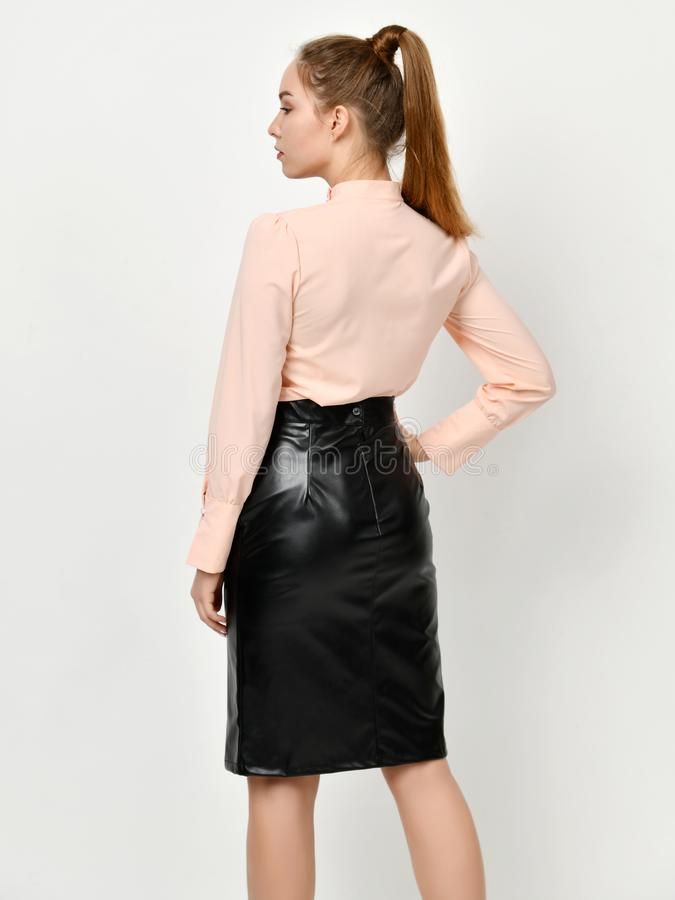 Young beautiful woman posing in new casual office cloth and leather skirt back side rear view stock image