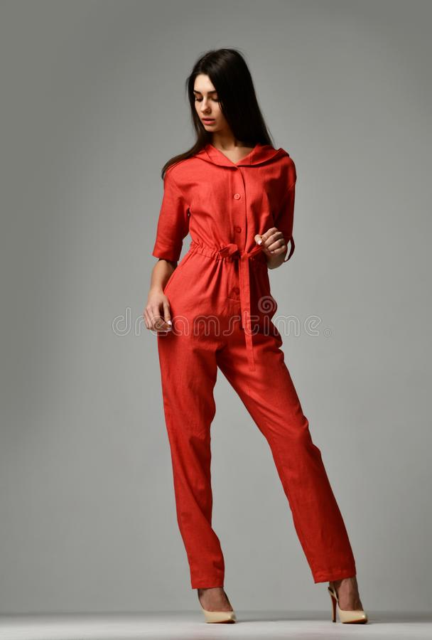 Young beautiful woman posing in new red fashion costume dress with pants and hood stock images
