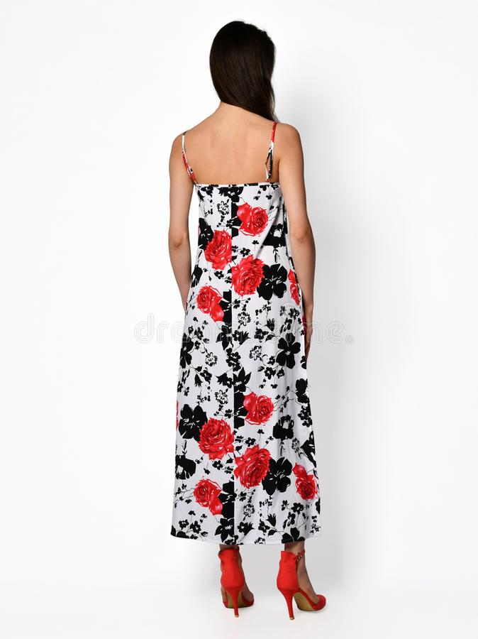 Young beautiful woman posing in new casual red flower pattern fashion dress back side rear view stock photography