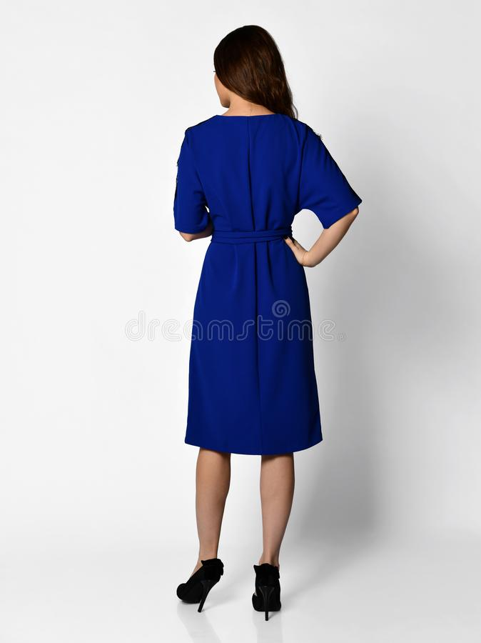 Young beautiful woman posing in new casual winter blue dress back side rear view royalty free stock photography