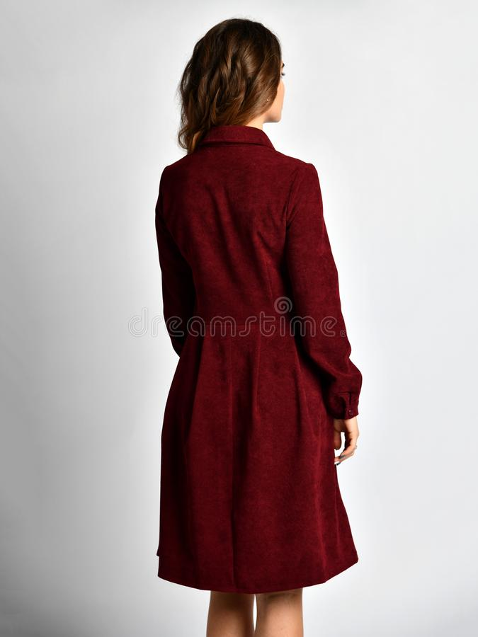 Young beautiful woman posing in new casual winter red dress back side rear view royalty free stock photography