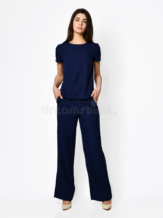 Young beautiful woman posing in new dark blue blouse with pants fashion casual costume royalty free stock photos