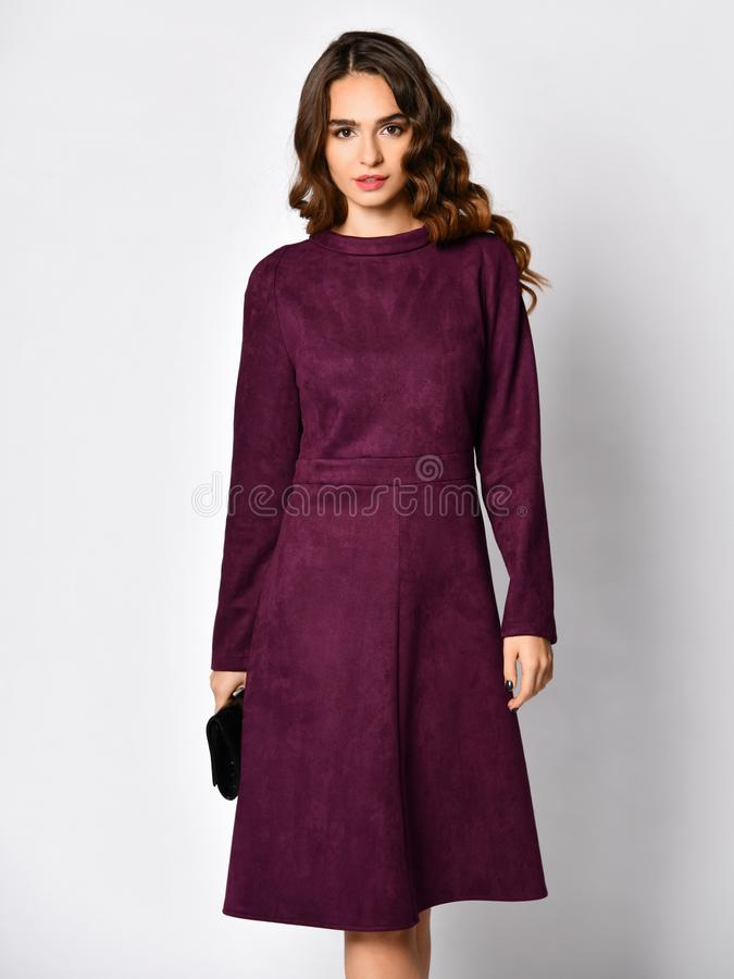 Young beautiful woman posing in new dark purple fashion winter dress. With choker on a white background royalty free stock photos
