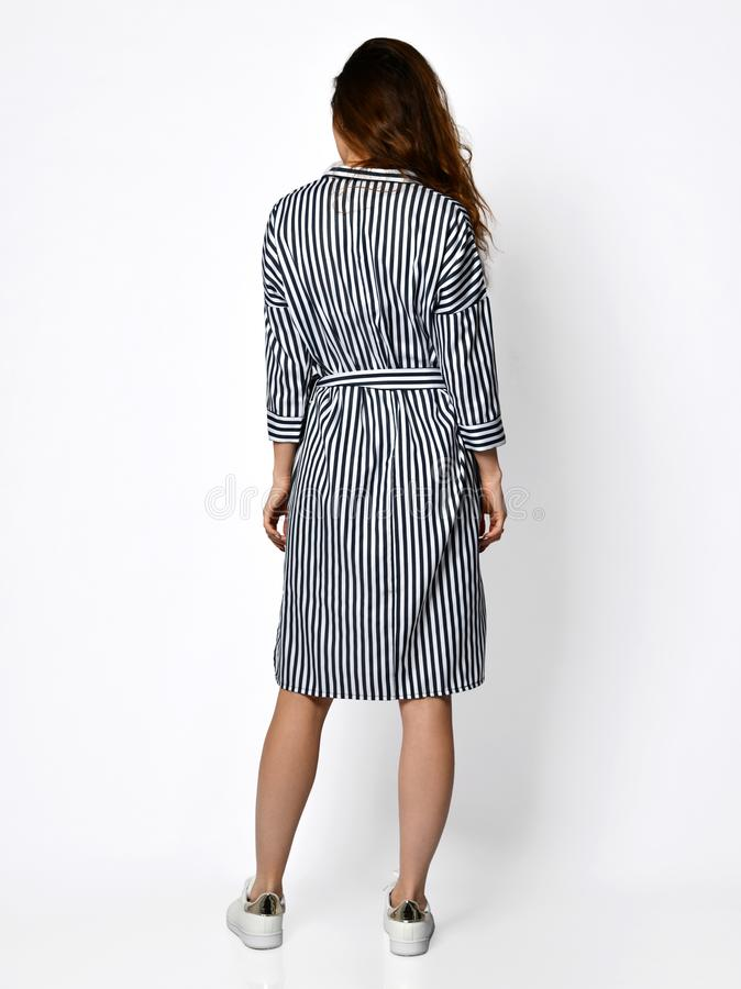 Young beautiful woman posing in new design casual stripes spring dress back view on grey royalty free stock photos