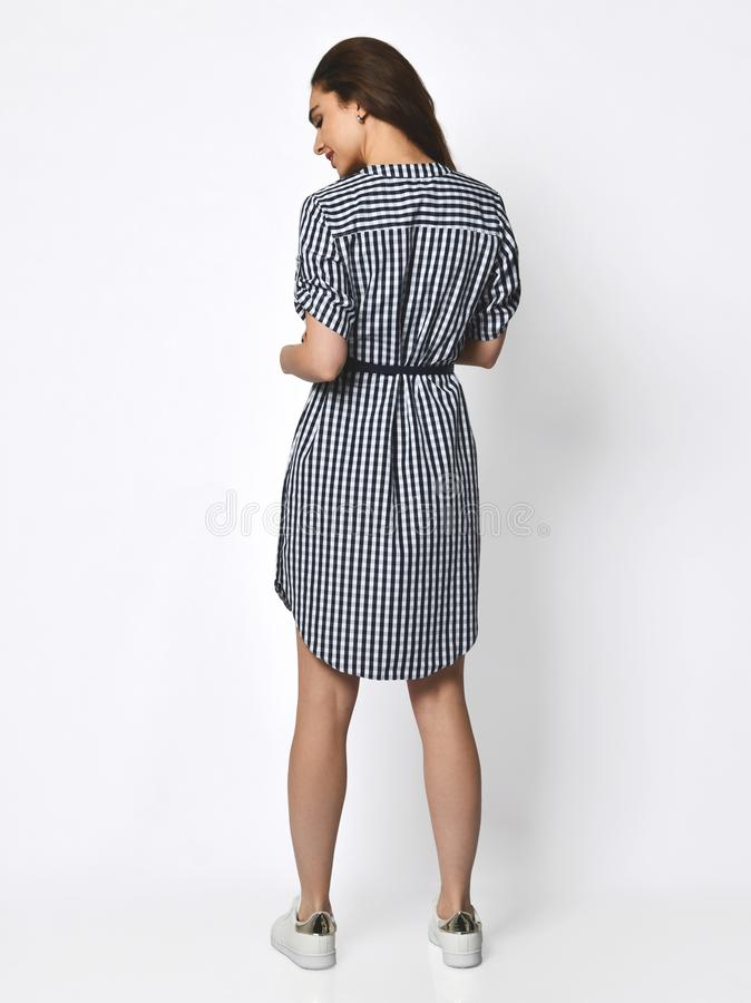 Young beautiful woman posing in new design casual stripes spring dress back view on grey royalty free stock photo