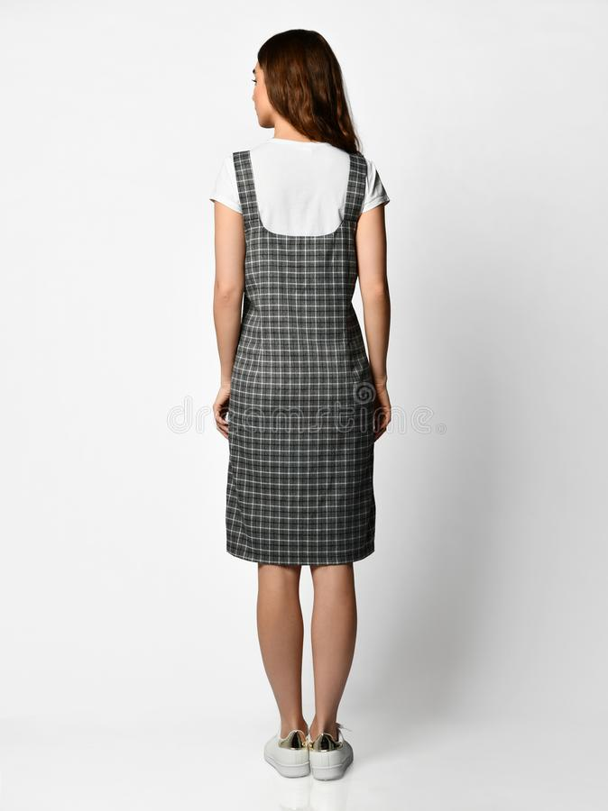 Young beautiful woman posing in new fashion plaid skirt and white blouse full body back side rear view royalty free stock photo