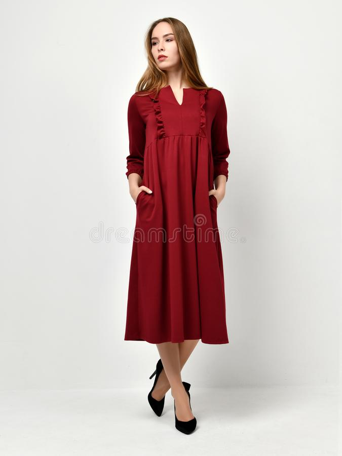 Young beautiful woman posing in new fashion red pattern winter dress stock image