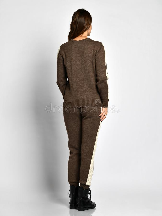 Young beautiful woman posing in new gray fashion winter knitted suit full body back side from behind stock image