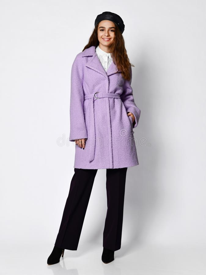 Young beautiful woman posing in new medium length fashion casual pink winter jacket coat, beret and dark trousers stock photo