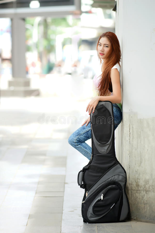Young beautiful woman posing outdoor with her guitar gig bag royalty free stock image