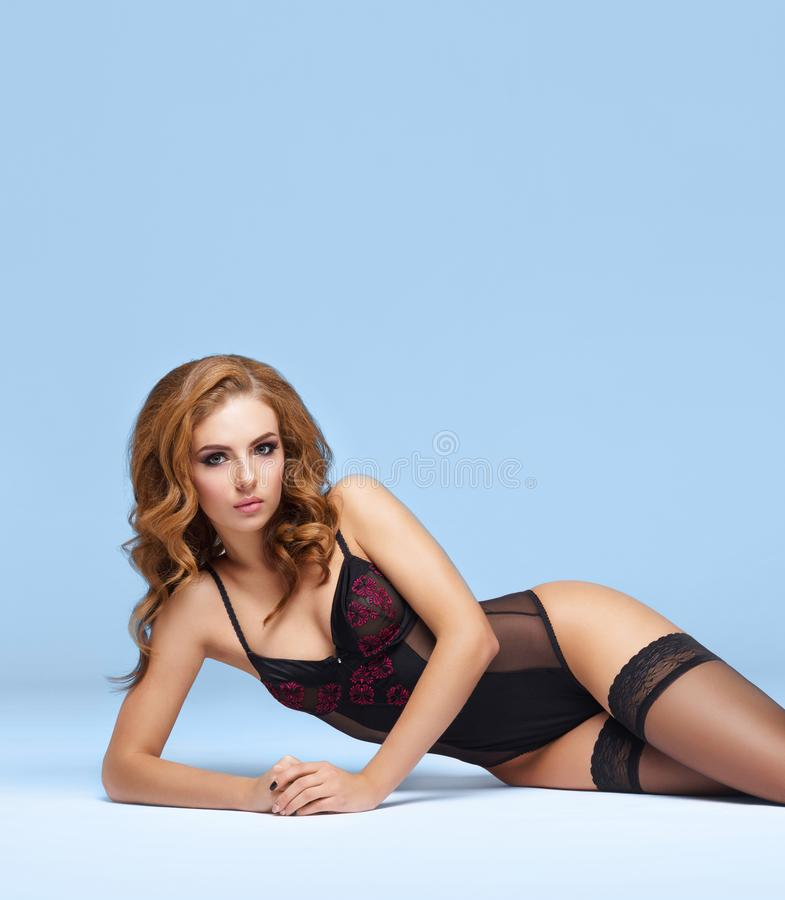 Young beautiful woman posing in sexy lingerie over colored background in studio. Girl in underwear. stock photography