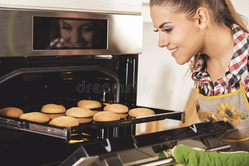 Young beautiful woman pulls cookies from the oven royalty free stock photo