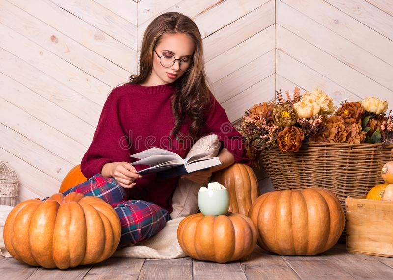 Young beautiful woman with pumpkins. Beautiful girl with glasses reads a book. Young pretty woman reading a book. royalty free stock image