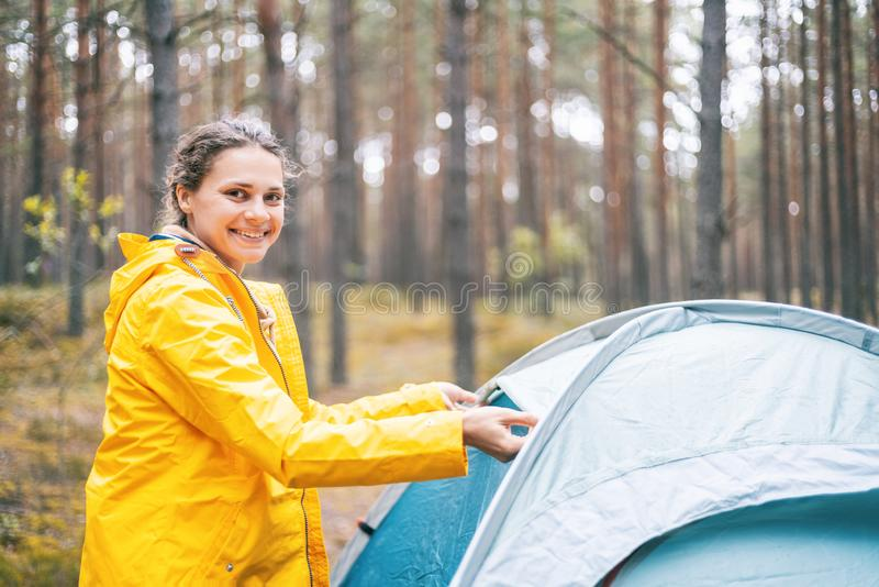 Young beautiful woman puts up a tent in the forest, camping, solo travel, nature-nature concept stock images