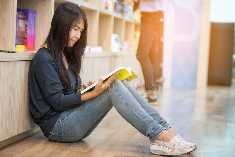 Young beautiful woman reading book while sitting on floor in library royalty free stock images