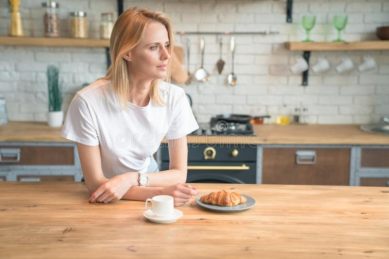 Young beautiful woman is reading her morning press while having breakfast in the kitchen. coffee with croissants. wearing white stock image