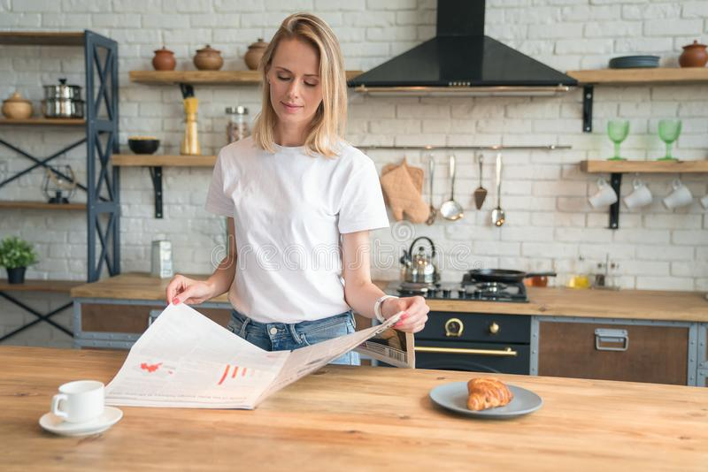 Young beautiful woman is reading her morning press while having breakfast in the kitchen. coffee with croissants. wearing white royalty free stock image