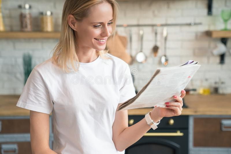 Young beautiful woman is reading her morning press and smiling while having breakfast in the kitchen. wearing white shirt stock images