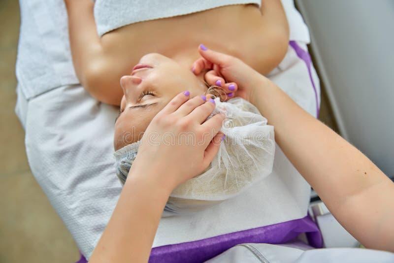 Young beautiful woman receiving facial massage at spa salon stock photo