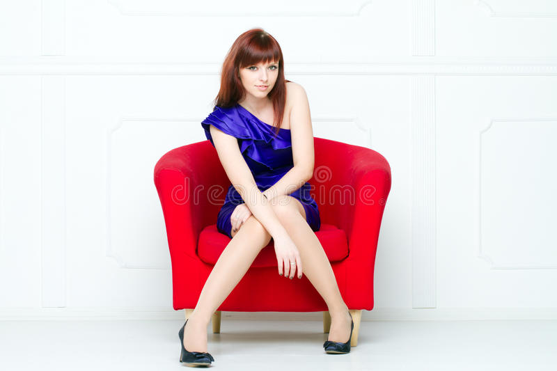 Young beautiful woman in a red chair stock photo