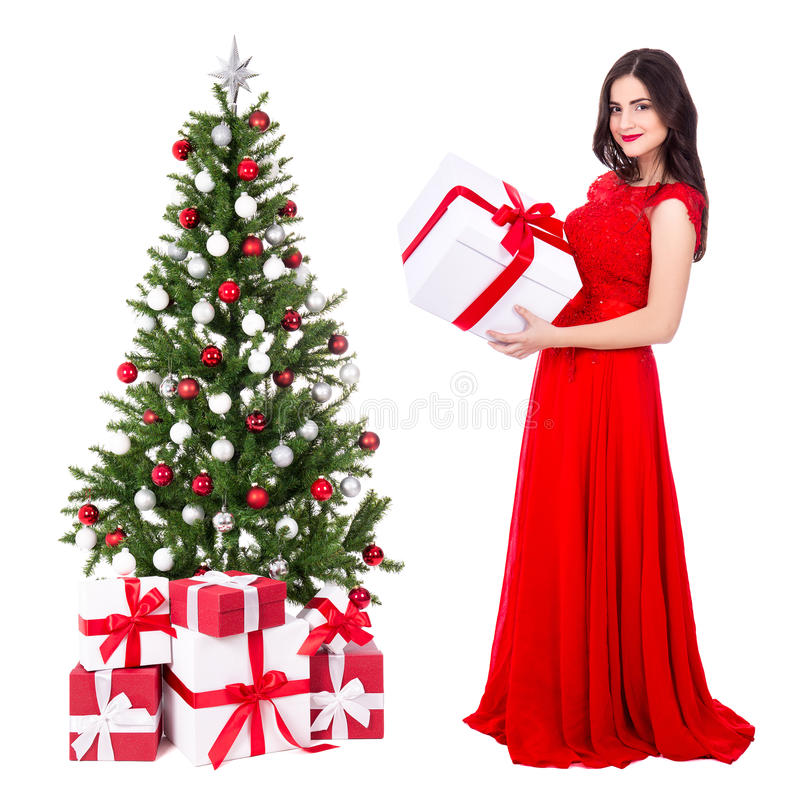 young beautiful woman in red dress with big gift box and decorated christmas tree isolated on white royalty free stock photos