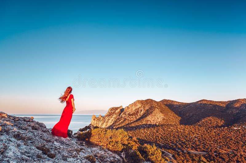 Young beautiful woman in red dress looking to mountains sea stock images
