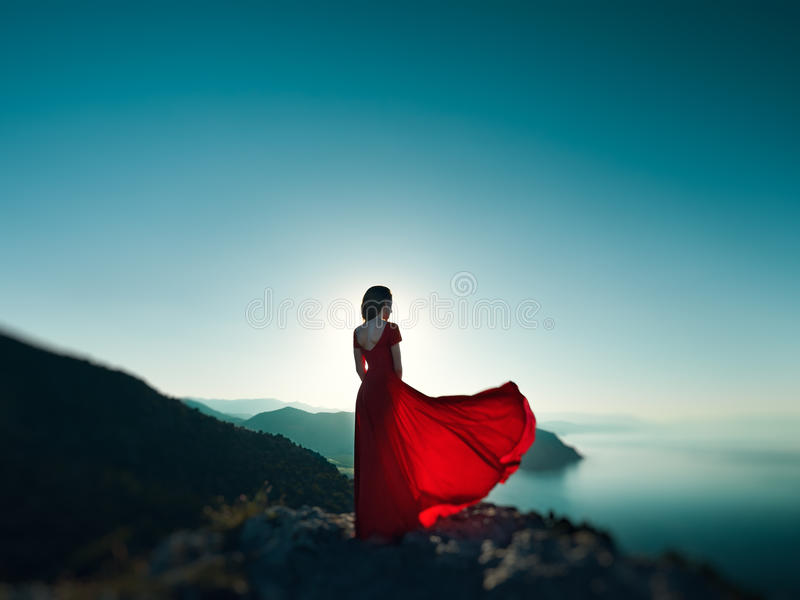 Young beautiful woman in red dress looking to mountains sea. Girl on the nature on blue sky background. Fashion photo stock photos
