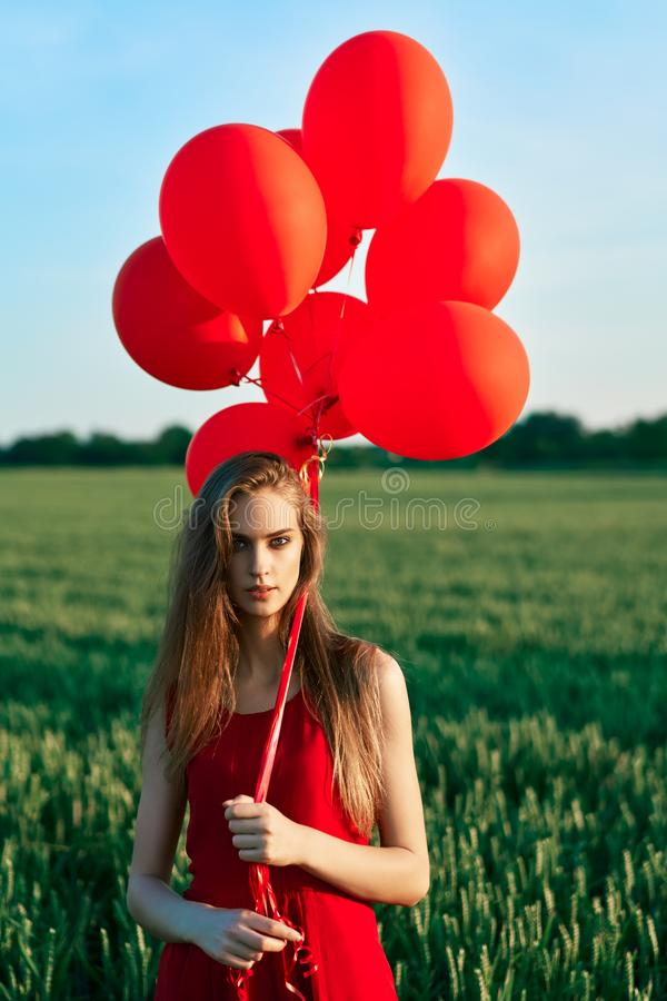 Young beautiful woman in red dress posing in green field with red balloons stock photography