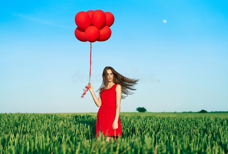 Young beautiful woman in red dress posing in green field with red balloons royalty free stock image