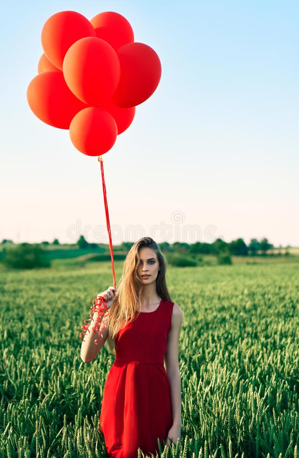 Young beautiful woman in red dress posing in green field with red balloons stock image