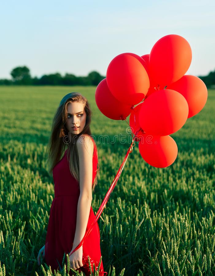 Young beautiful woman in red dress posing in green field with red balloons stock images