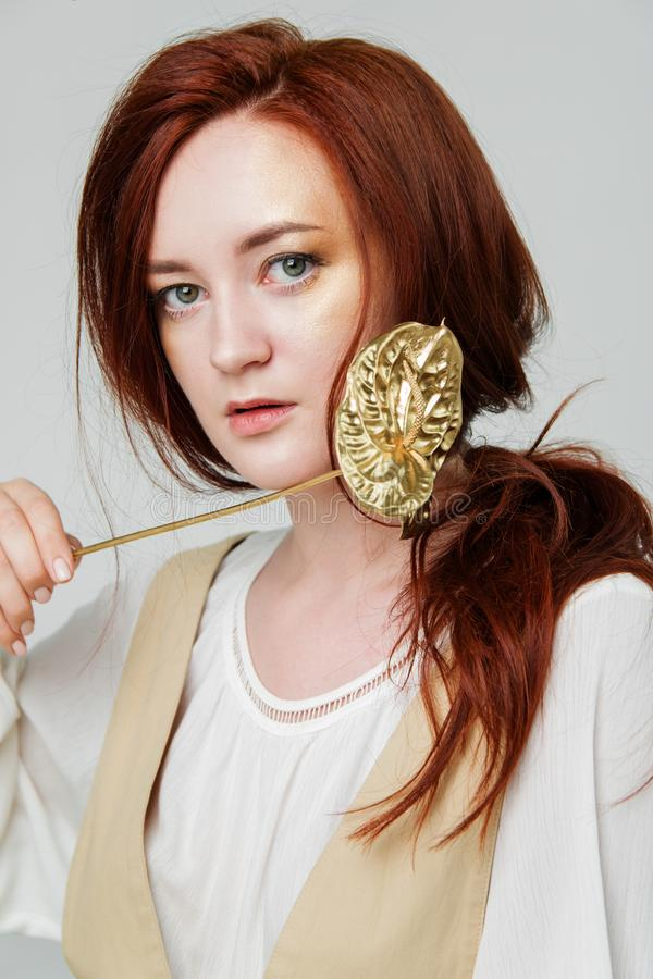Young beautiful woman has red hair creative gold make up are posing in a studio with flowers stock photo