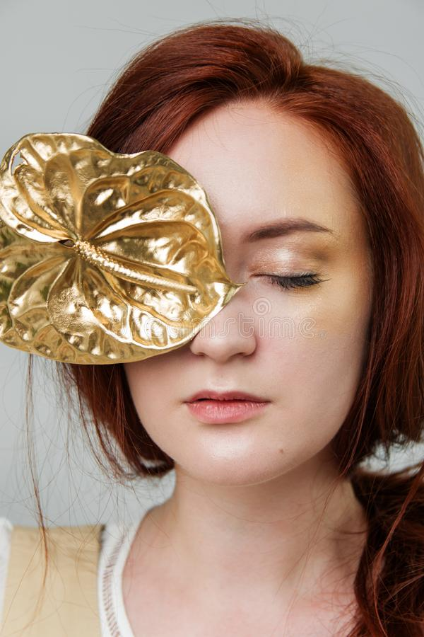 Young beautiful woman has red hair creative gold make up are posing in a studio with flowers royalty free stock photography