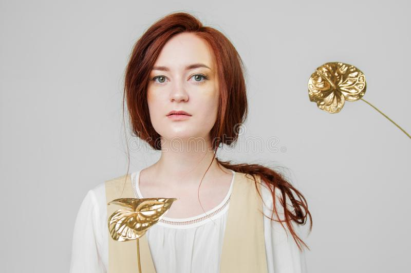 Young beautiful woman has red hair creative gold make up are posing in a studio with flowers royalty free stock photos