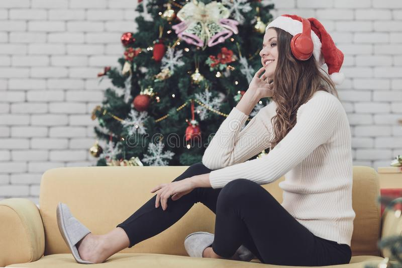 Young beautiful woman in red hat sitting on sofa between christmas trees and listening to music with headphone in front of hugh c royalty free stock photos